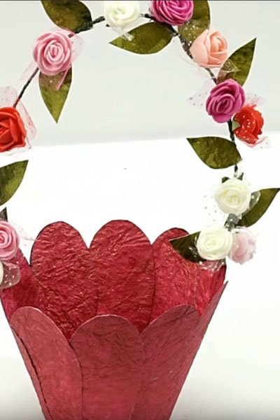 Stick the artificial flowers and leaves on the basket handle